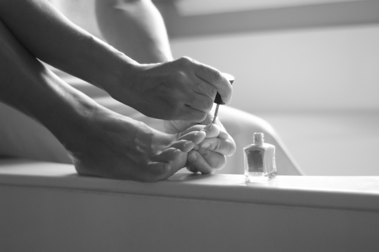 Black and white photo of painting toenails