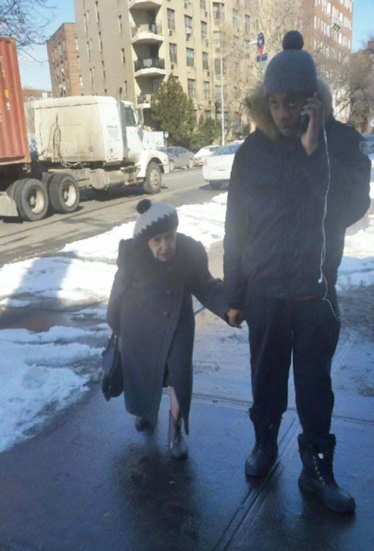 Image of elderly woman walking with young man