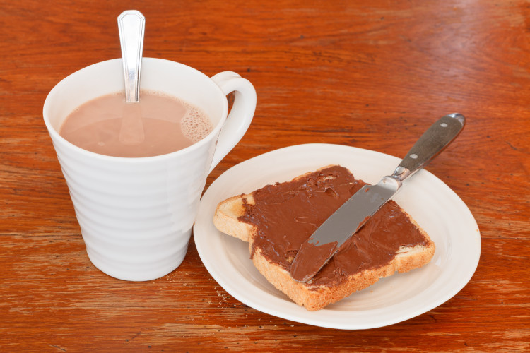 cup of hot chocolate and sweet sandwich from fresh toast with chocolate spread, table knife on wooden table