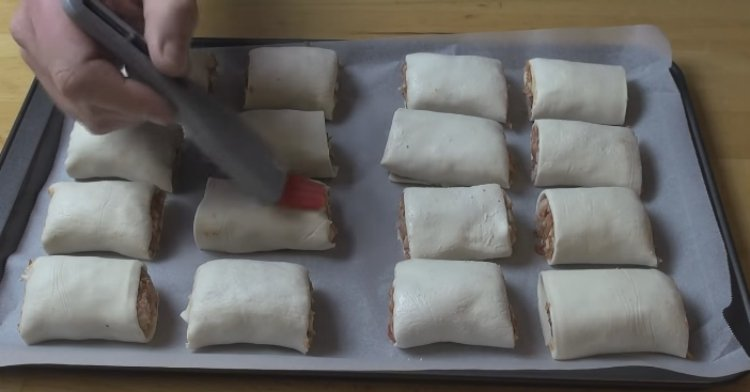 Brushing the tops of the uncooked sausage rolls with egg.