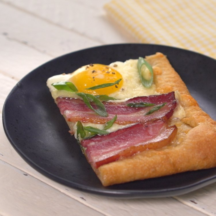 Piece of bacon and egg breakfast tart on black plate