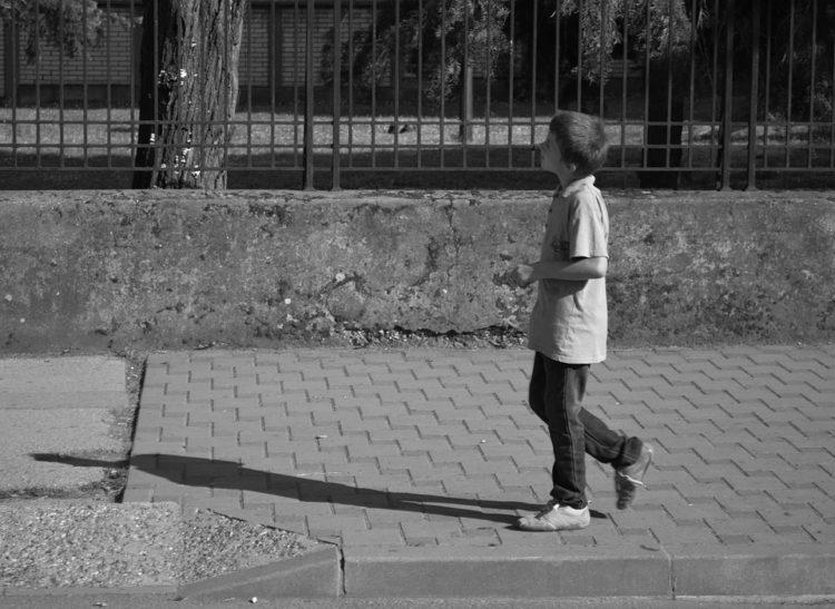 Image of boy walking alone, black and white.