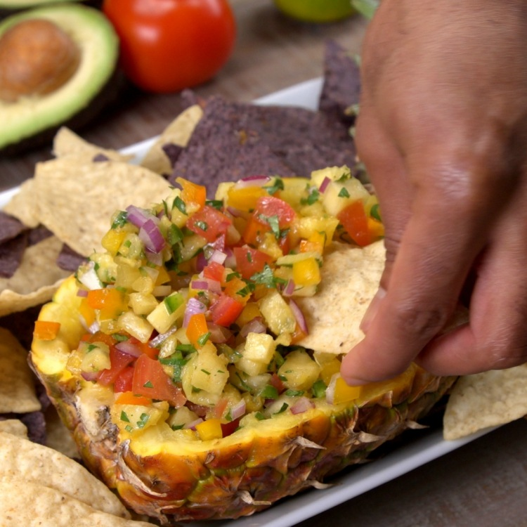 Eating pineapple salsa with tortilla chip