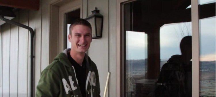 Zack stands and smiles next to clean window