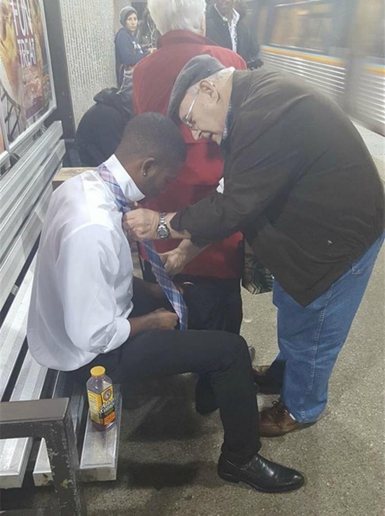 Image of elderly man tying young man's tie