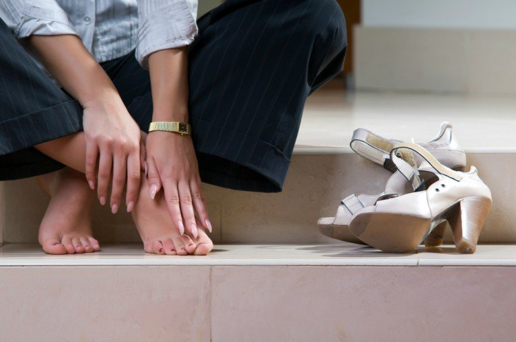 Woman rubbing sore foot because of shoes.