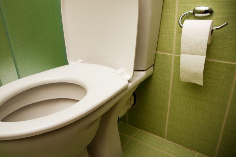 Toilet in green tiled bathroom.