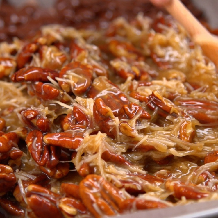 Pecan halves mixed with eggs, brown sugar, corn syrup, butter and shredded coconut