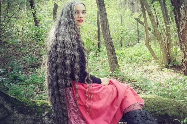Shot of woman in forest long gray hair.