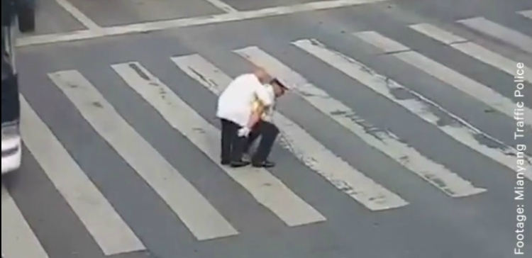 Image of police officer helping man across the street by giving him a piggy back ride