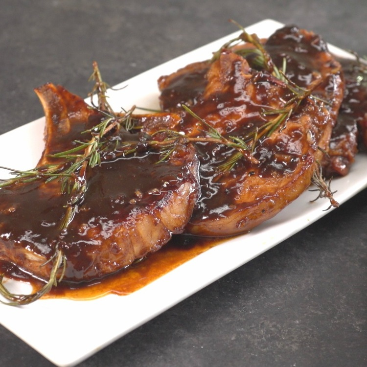 Pork chops glazed with honey balsamic sauce on a white plate