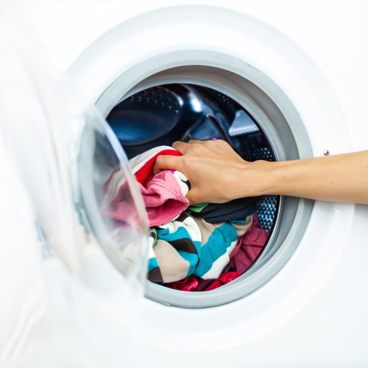 Houswork: Fetail of Female Doing Luandry, while Putting Clothes into the Laundry Machine