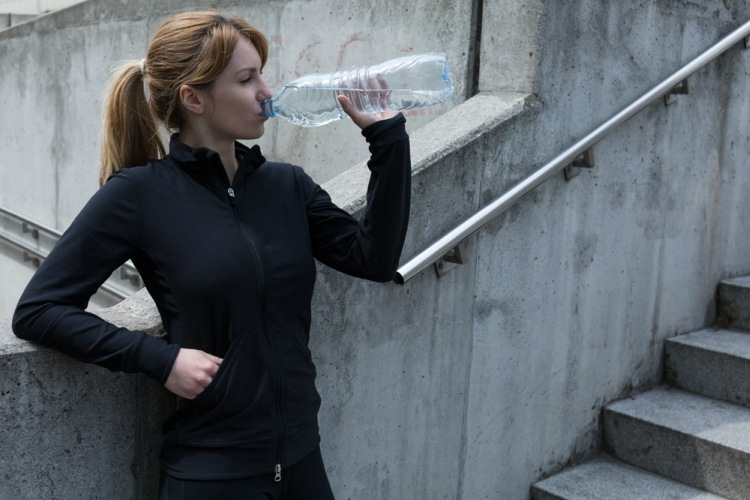 Woman drinking water to stay hydrated after jogging