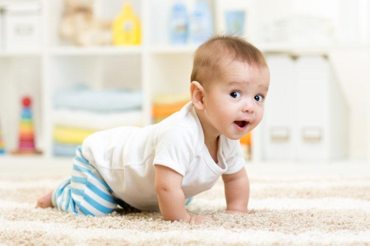 Image of crawling funny baby boy indoors at home
