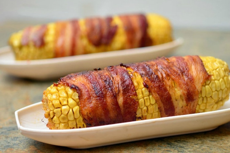 Corn on the cob wrapped in bacon with a chipotle-honey glaze