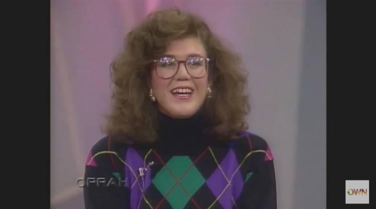 Eighties-era giant hair, glasses and sweater