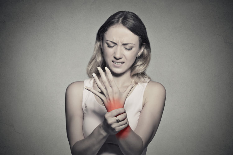 Image of young woman holding her painful wrist isolated on gray wall background.