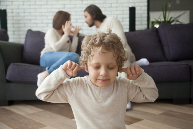 Image of Little boy puts fingers in ears not to hear parents fighting at background, upset tired son suffering from mom and dad arguing, parental conflicts hurt kid, family divorce effect on children concept