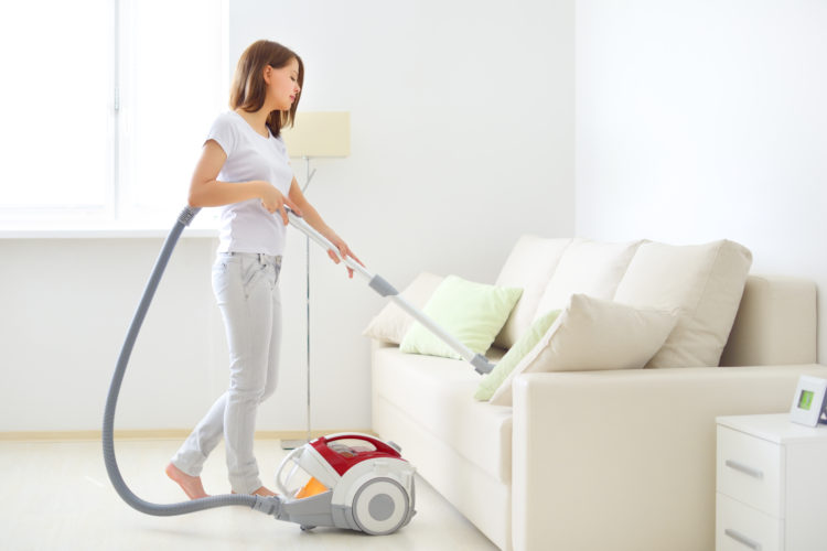 Image of teen vacuuming couch