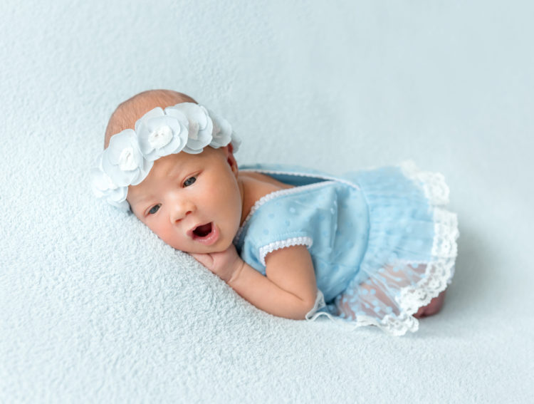 Image of Cute newborn baby girl in a blue dress