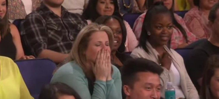 Mary covers her face with her hands while seated in the audience