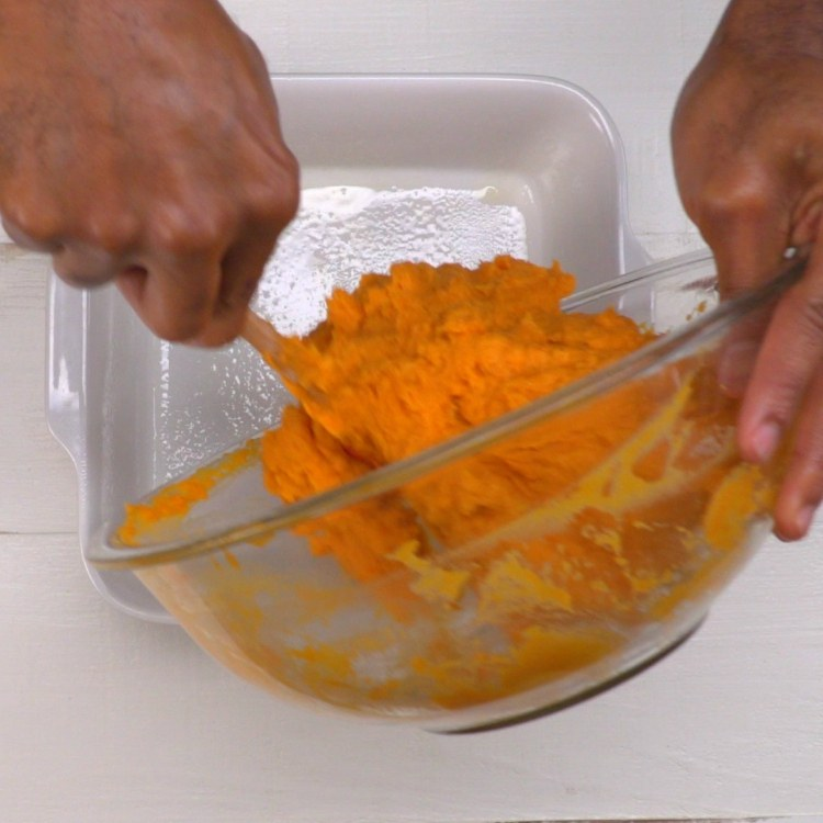 Filling 8-by-8-inch dish with sweet potato filling