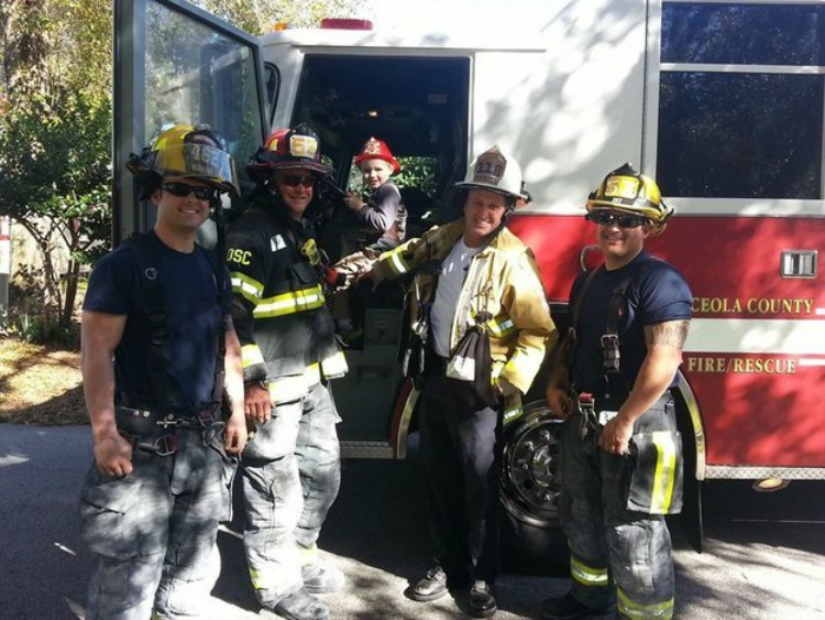 Image of firefighters and little boy