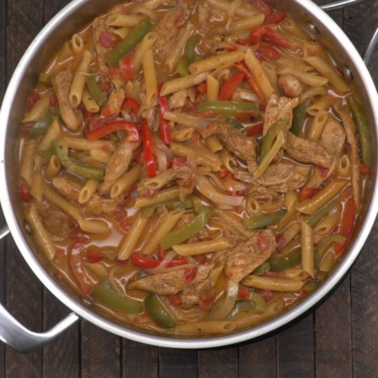 Chicken fajita pasta cooking in sauté pan with sauce