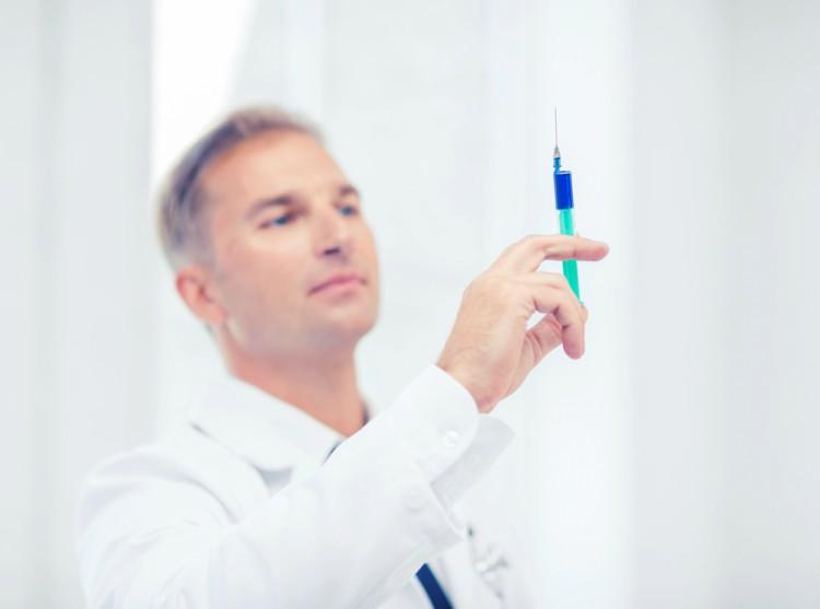 Doctor holding syringe.