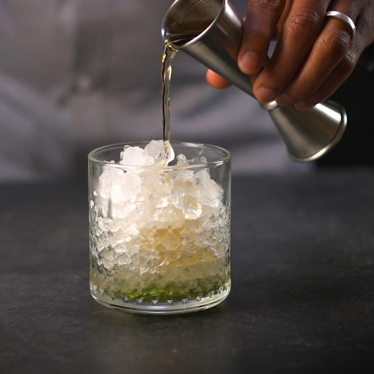 Mint Julep pouring bourbon into glass with crushed ice