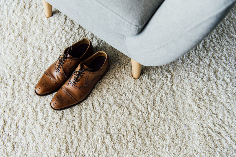 Image of carpet with shoes and couch