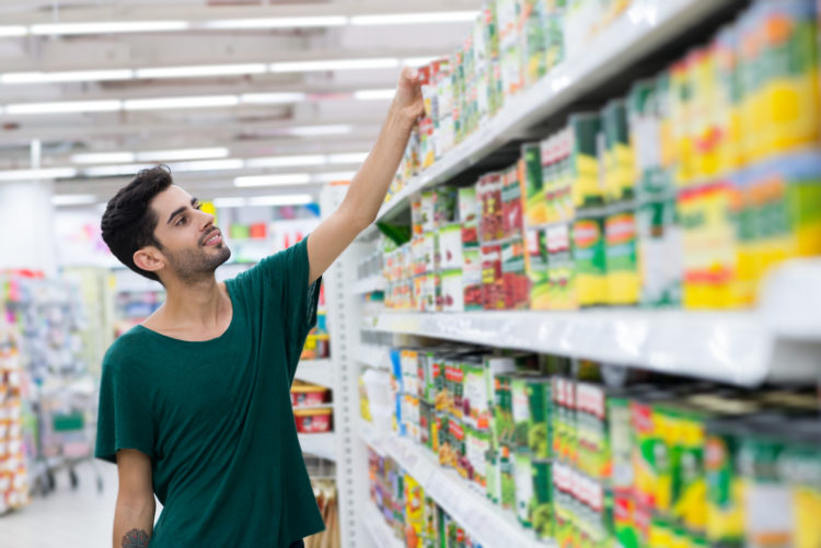 Image of young customer taking canned food from the shelf in the store