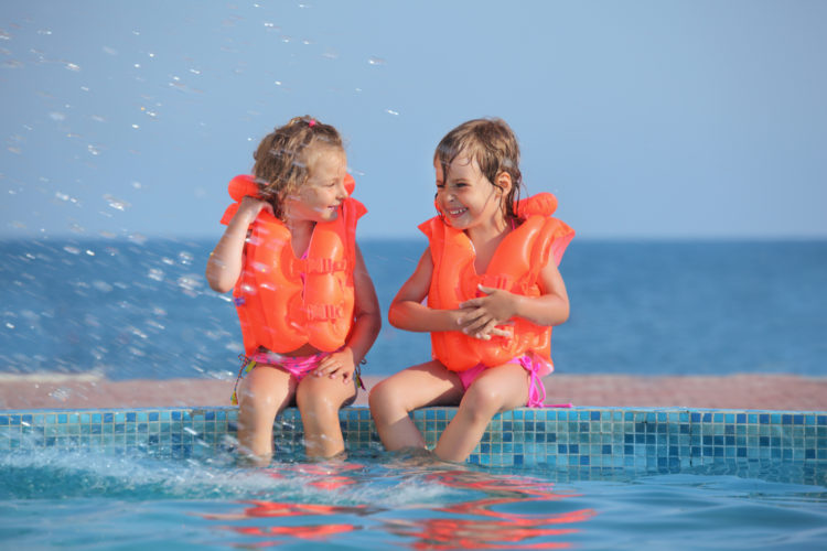 Image of two little girls in lifejackets sitting on ledge pool on resort, Looking against each other