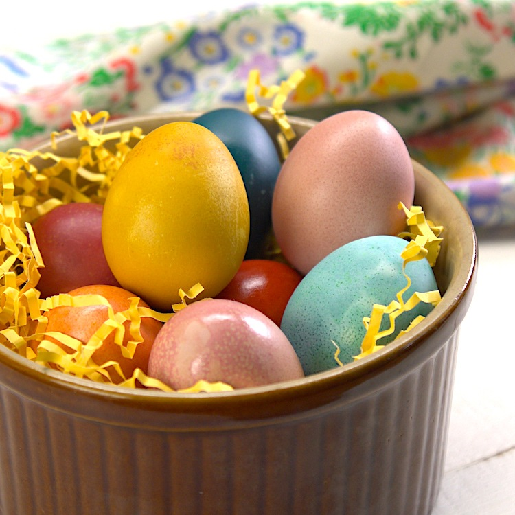Naturally Dyed Easter Eggs in bowl close-up floral linen in background