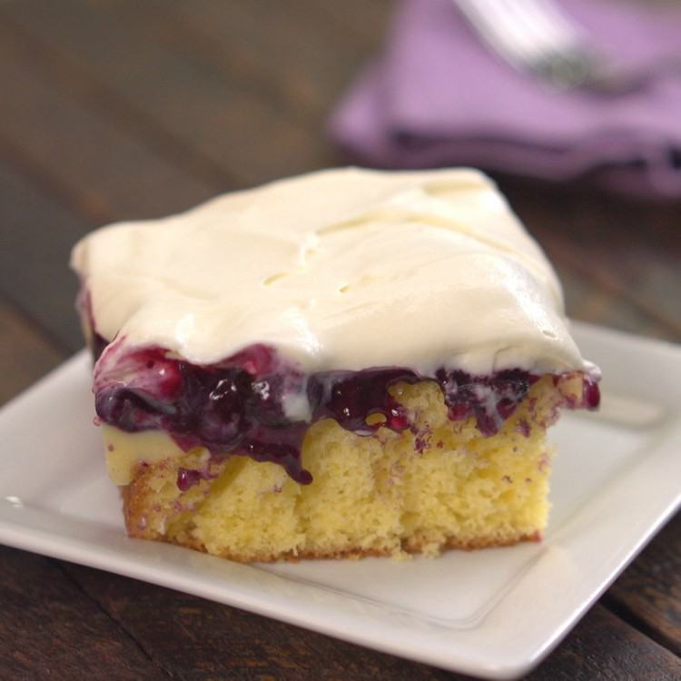 Lemon pudding poke cake topped with blueberry sauce and cream cheese frosting