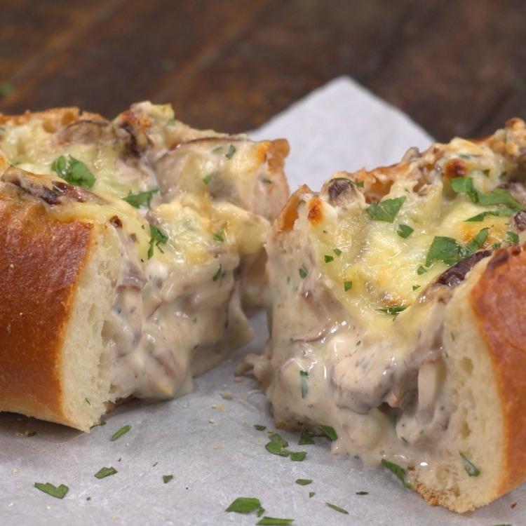 Loaf of creamy garlic mushroom-stuffed bread cut in half