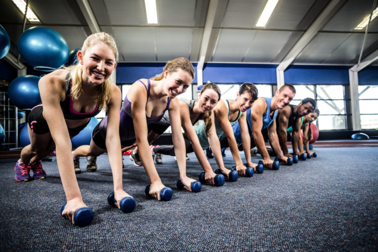 Image of Fitness class in plank position with dumbbells at the gym