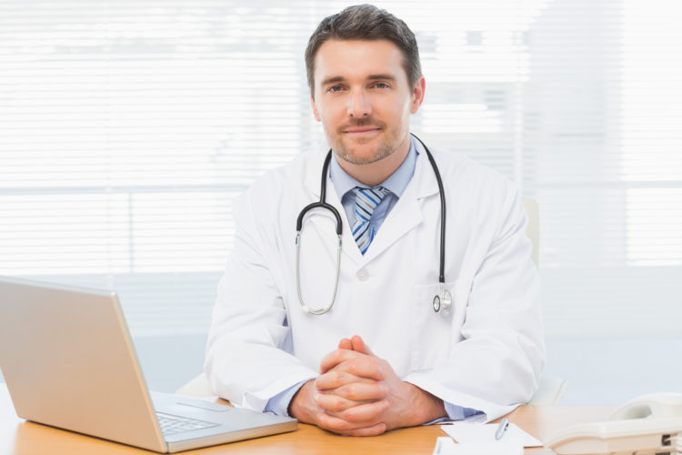 Image of a smiling male doctor with laptop sitting at desk in medical office