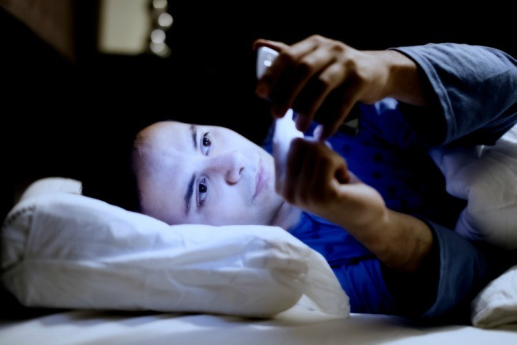 Image of guy in the bed with phone.