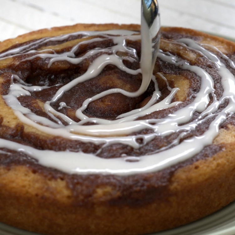 Drizzling cinnamon roll cake with icing