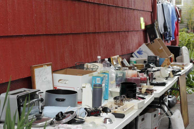 Variety of old, unwanted objects on two tables near a wall of a house in a driveway being displayed for sale at a yard sale.
