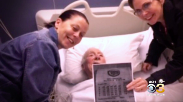 Image of Earl Livingston at hospital with winning lotto ticket and nurse