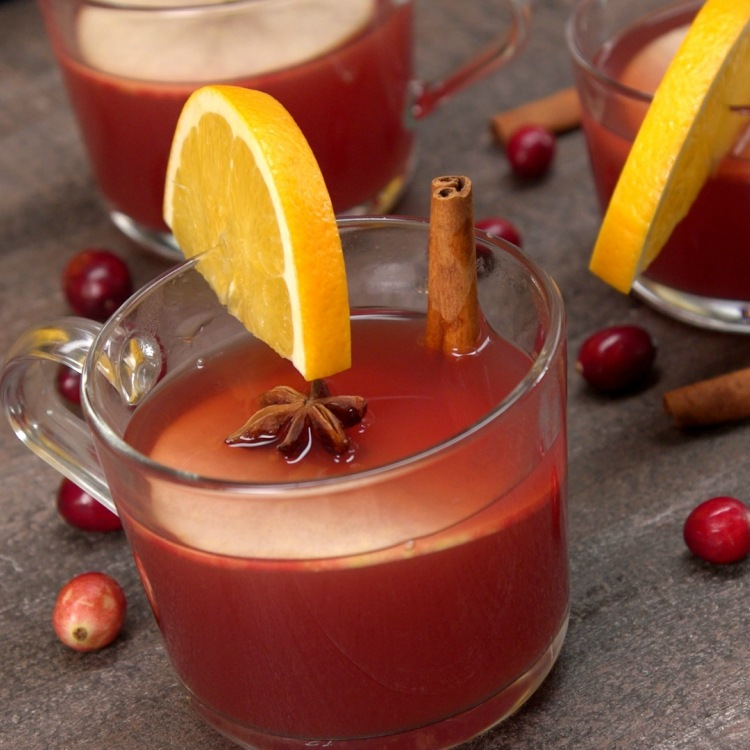 Cup of spiced cranberry apple cider made in slow cooker