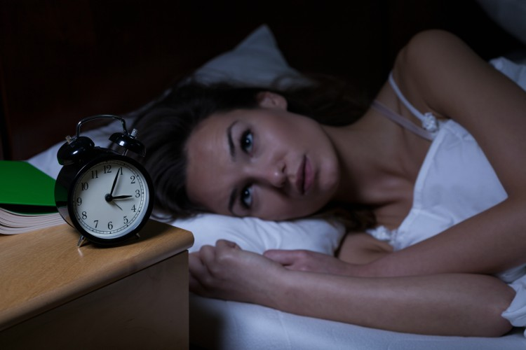 Image of woman in bed awake.