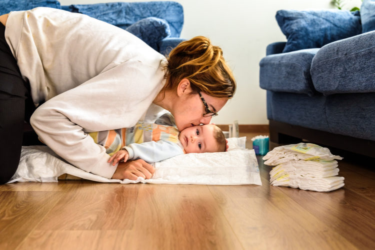 Image of Mom changing the diaper to her daughter, on the floor of her living room and giving her kisses.