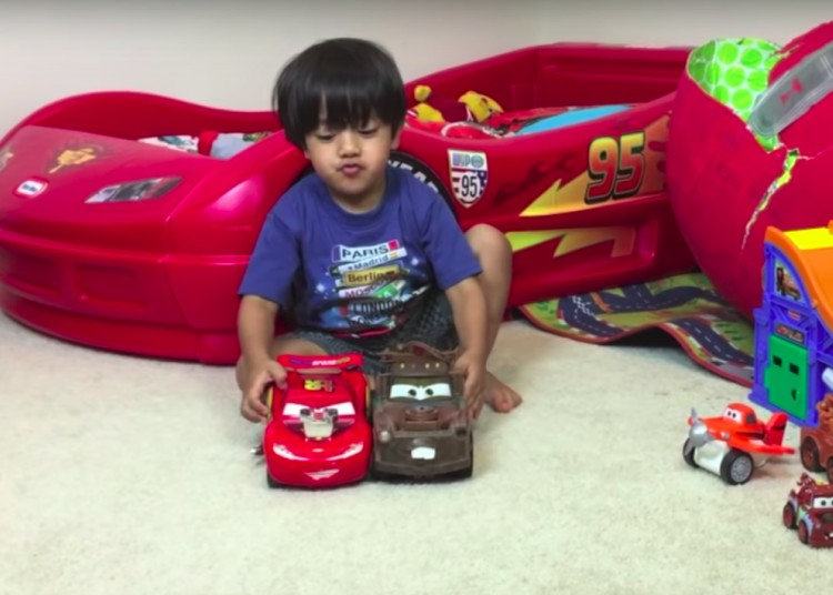 Image of Ryan from Ryan ToysReview playing with toy cars