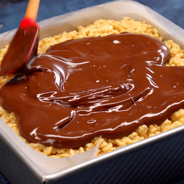 We mixed peanut butter into our rice krispie treats, stuffed them with a layer of peanut butter cups, then topped them with melted chocolate.
