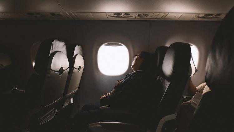 Woman sleeping on plane.