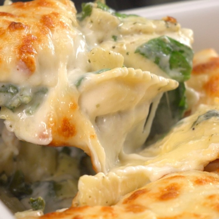 Spooning out a serving of creamy spinach artichoke ravioli bake
