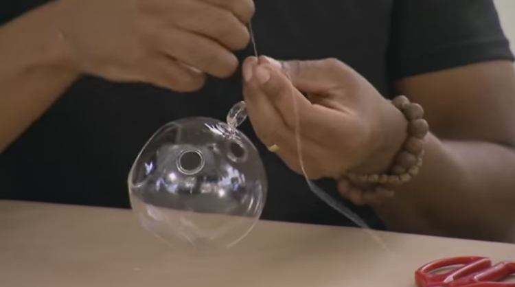 Knot the fishing line onto the glass orbs three or four times
